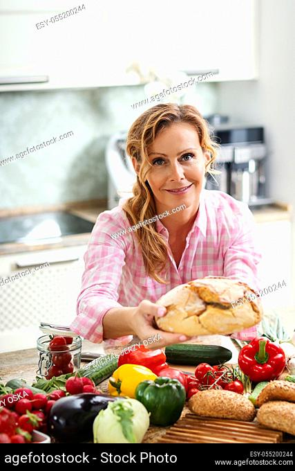 woman at the table with vegetables holds fresh and fragrant bread in her hands
