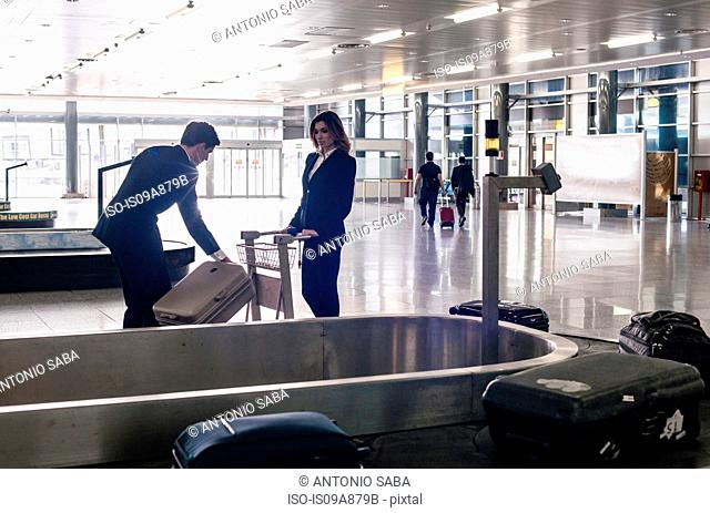 Businesspeople in airport at baggage reclaim