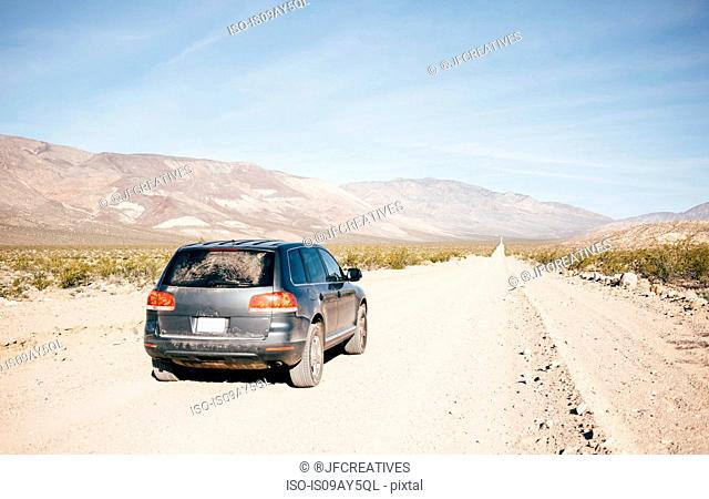 Off road vehicle on straight dirt track road in desert landscape, Olancha, California, USA