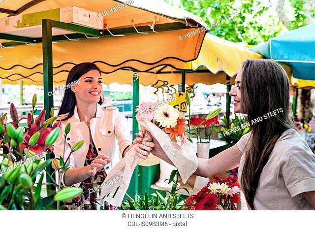 Stall holder handing female tourist bunch of flowers at market stall, Split, Dalmatia, Croatia
