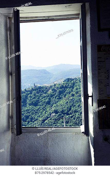 Early morning view of a village with the Church seen from behind a window. San-Gavino-di-Tenda, Corsega, France