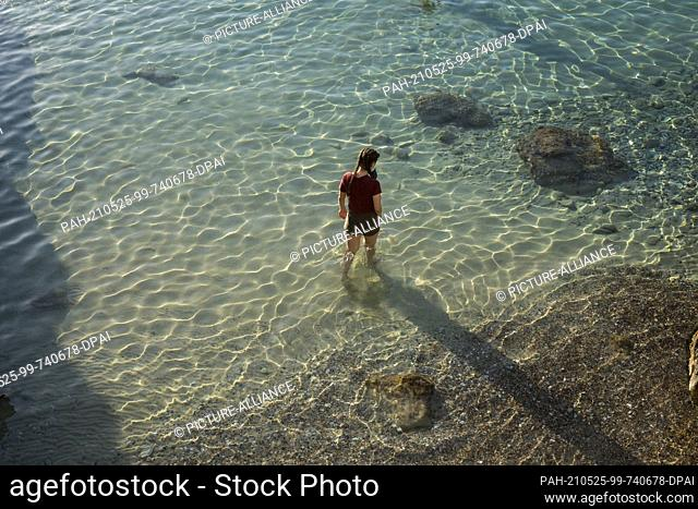 23 May 2021, Greece, Limeni: A woman walks on the beach of Limeni, a small fishing port on the Mani peninsula. Photo: Socrates Baltagiannis/dpa