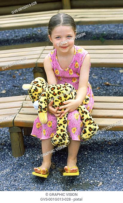 Portrait of a young girl smiling sitting on stairs holding a stuffed toy