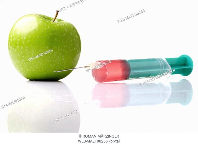 Syringe injecting liquid in apple