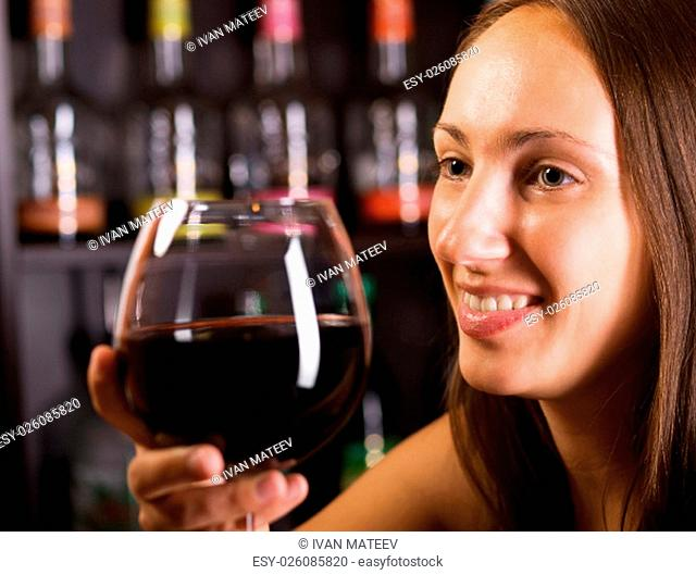 Portrait of young woman with wine glass at the bar