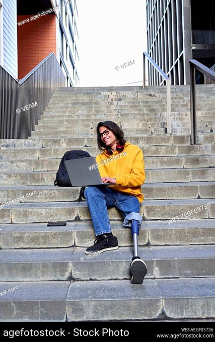 Smiling young disabled man with artificial limb using laptop while sitting on steps in city