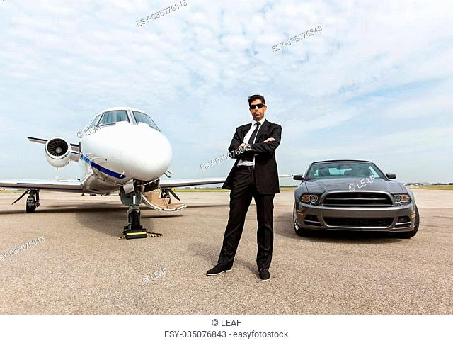Full length of confident businessman standing by car and private jet at airport terminal