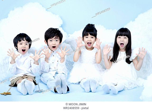 Four children in angel costume seated together in surprise in the background representing heaven