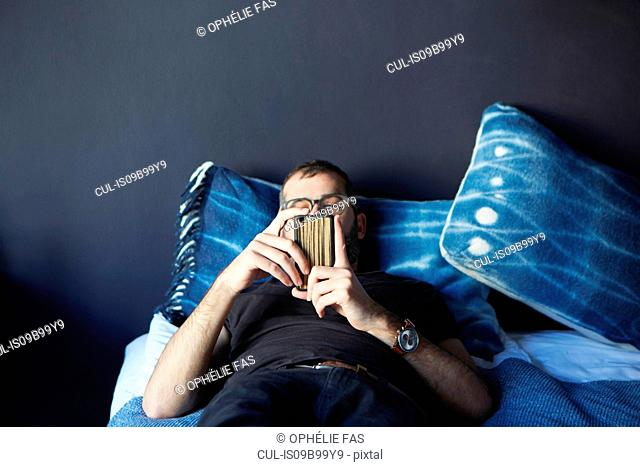 Young man lying on bed looking at smartphone