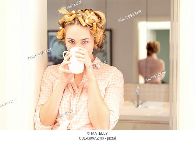 Young woman, foam rollers in hair, drinking hot drink