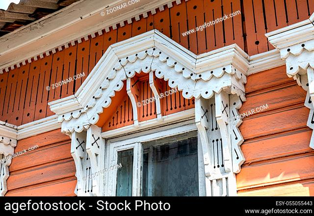 Russian traditional wooden architecture. Facade of an old house decorated with wooden carvings, platbands, wooden lace ornament