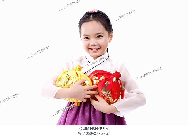 a girl in Korean traditional costume holding a luck bags