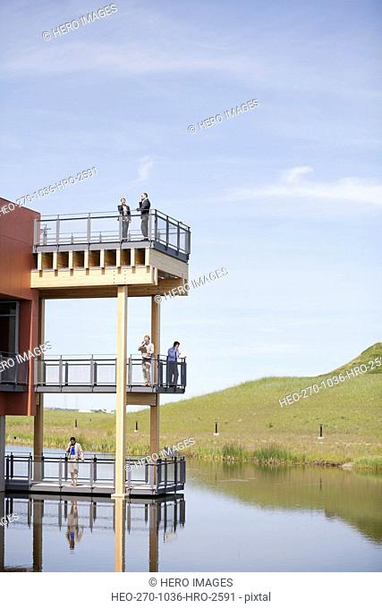 Business people standing on multiple office balconies