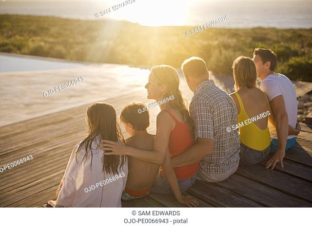 Family sitting on deck by swimming pool