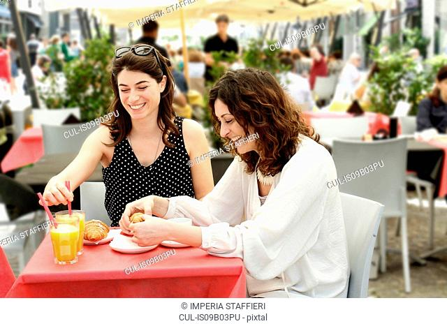 Two women chatting and having breakfast at sidewalk cafe, Milan, Italy
