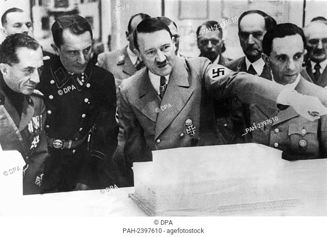 Adolf Hitler (m) explains the model of a building to the Italian Economy Minister Lantini (l) at the Second Exhibition for Art and Architecture (undated)