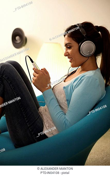 Singapore, Young woman listening to music in living room