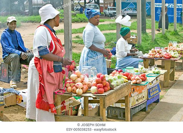 Black Zulu women street vendors in brightly colored clothes sell produce in Zulu village, Zululand, South Africa