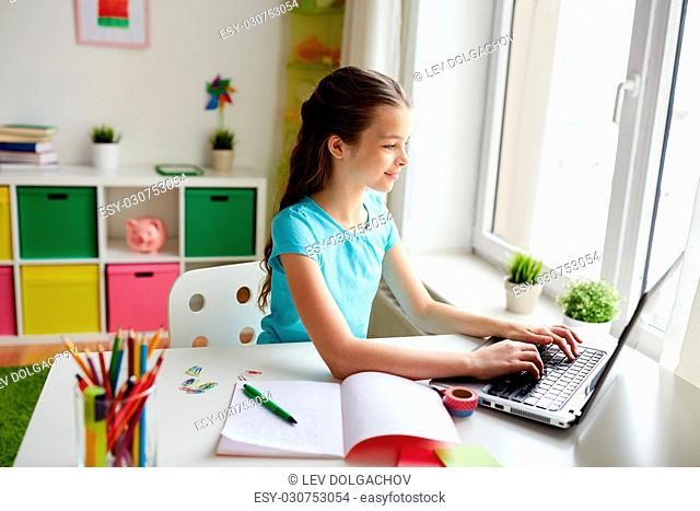 people, children, education and learning concept - happy girl typing on laptop and doing homework at home