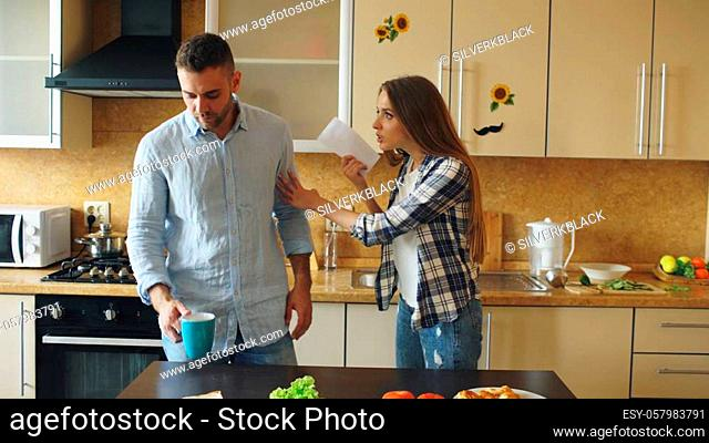 Young couple quarrels in the kitchen during breakfast time in the morning at home