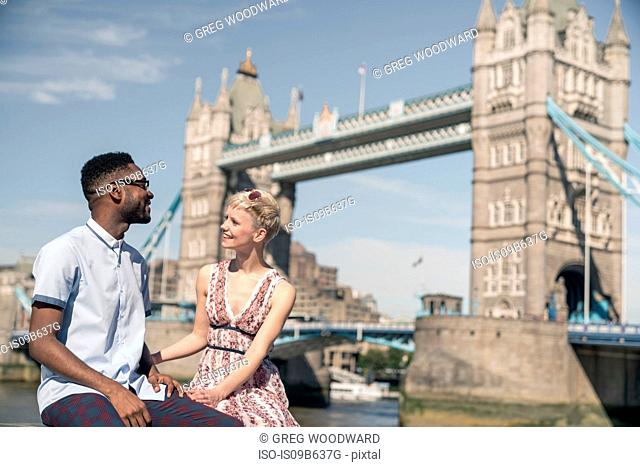 Young couple sitting on wall, smiling, Tower Bridge in background, London, England, UK