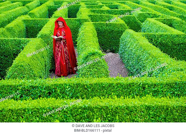 Woman in medieval costume reading book in hedge maze