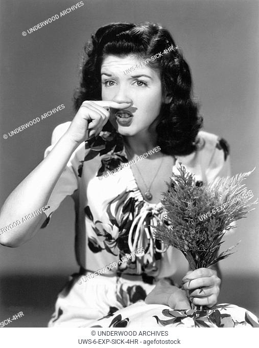 Hollywood, California: 1944.Actress Peggy Ryan tried to defuse a sneeze while holding a bouquet