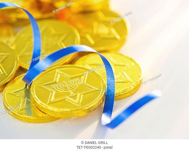 Studio Shot of chocolate coin and blue ribbon