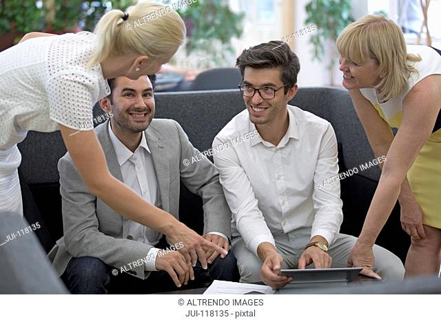 Businesspeople Meeting In Lobby Of Modern Office