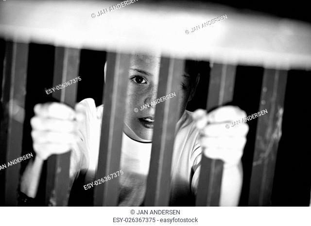 Black and white view on confused single male child imprisoned with hands grabbing jail cell bars