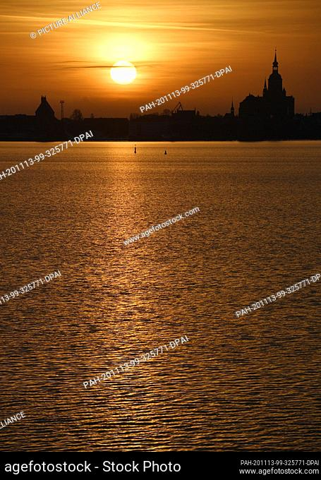 13 November 2020, Mecklenburg-Western Pomerania, Stralsund: Orange is the sky at sunset over the silhouette of the Hanseatic city of Stralsund with the...