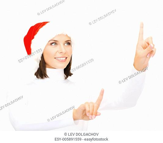 christmas, x-mas, winter, happiness concept - smiling woman in santa helper hat pressing vitrual button