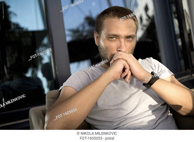 Portrait of serious man sitting in chair on balcony