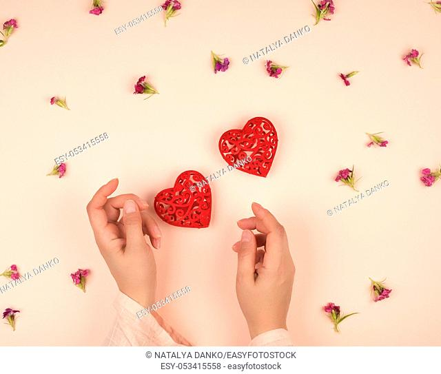 two female hands and red hearts, peach background with flowers, top view