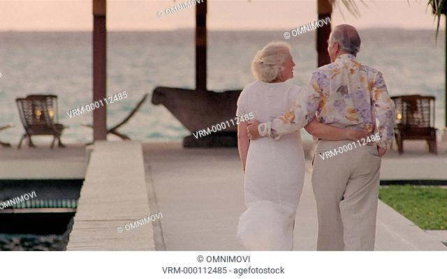 Senior couple walking and holding arms around each other