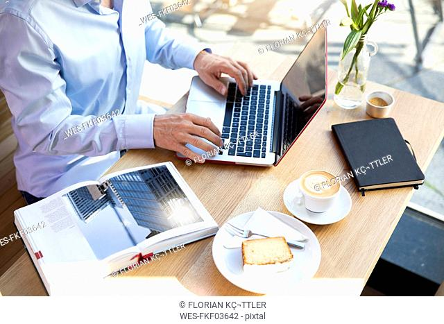Close-up of man using laptop in a cafe with book on table