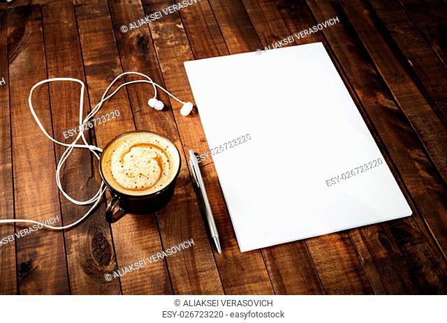 Blank stationery on vintage wooden table background. Blank paperwork mock-up. Blank letterhead, pen, headphones and coffee cup