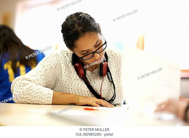 Young female student writing at desk in college classroom