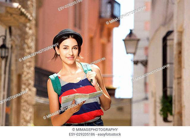 Portrait of a young travel woman walking in town with bag and map