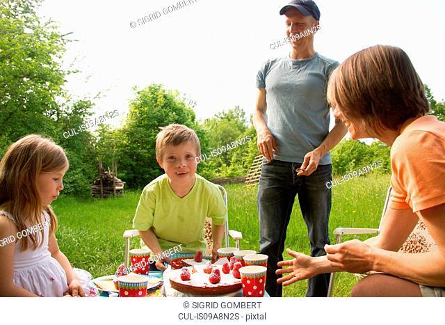 Family outdoors having birthday picnic