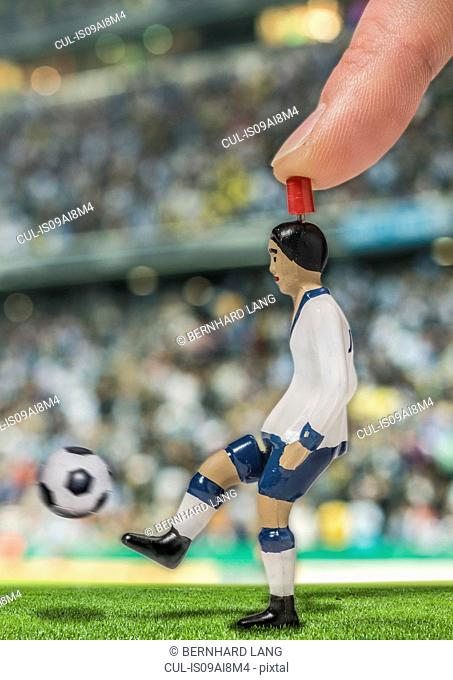 Digitally generated image of soccer player kicking ball in stadium