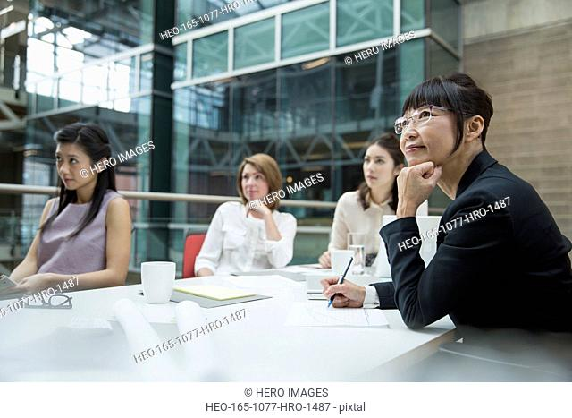 Businesswomen listening attentively in conference room meeting