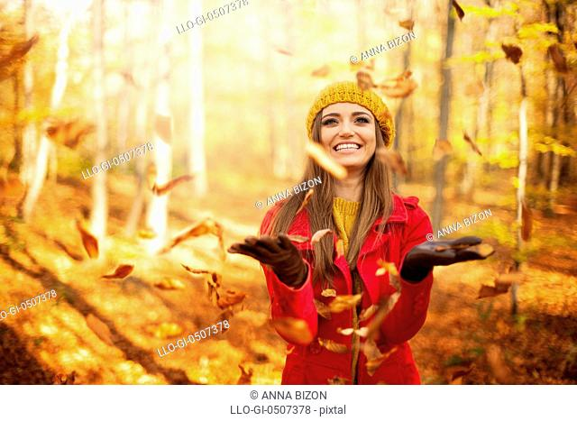 Happy woman throwing leaves, Debica, Poland