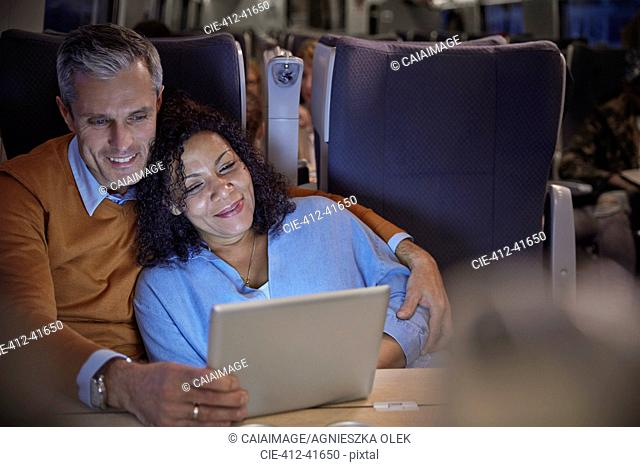 Affectionate couple watching movie on digital tablet on on passenger train at night
