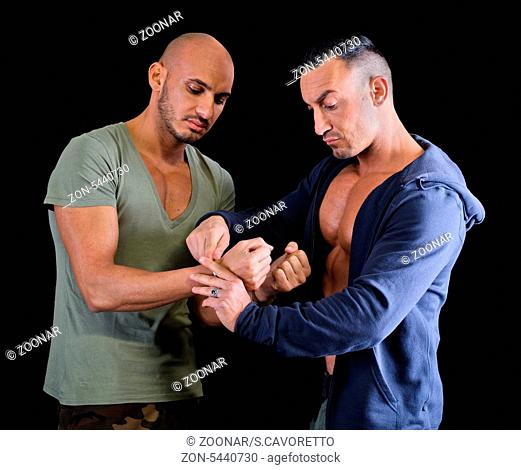 One muscular man putting handcuffs to another young man, dark background