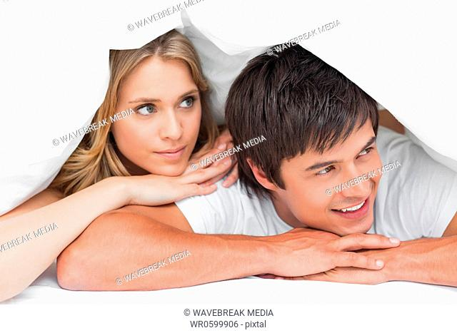 Man and woman resting their heads on their hands and looking to the side, smiling