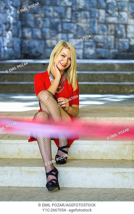 Candid shot young woman in Red dress sitting and smiling