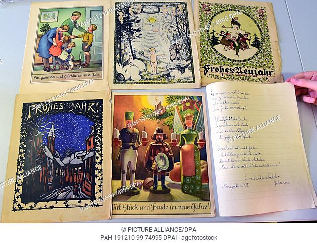 06 December 2019, Saxony, Delitzsch: In the Museum Barockschloss Delitzsch, staff member Mania Kurrey shows cards with New Year's wishes from the years...