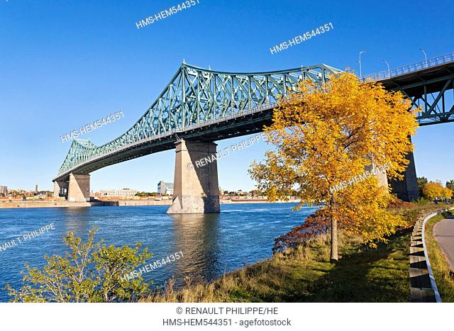 Canada, Quebec Province, Montreal, Jacques Cartier Bridge from the banks of the St. Lawrence River on Ile Sainte Helene, tree in Autumn colors