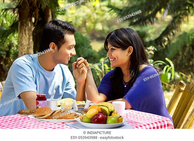 Couple holding hands on breakfast table